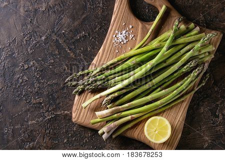 Bundle of young raw uncooked organic green asparagus with sliced lemon and sea salt on wooden chopping board over brown texture background. Top view. Healthy eating
