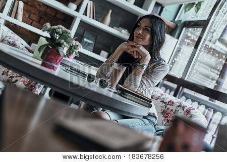 Thinking about... Attractive young woman looking away with a smile while sitting in restaurantThinking about... Attractive young woman looking away with a smile while sitting in restaurant