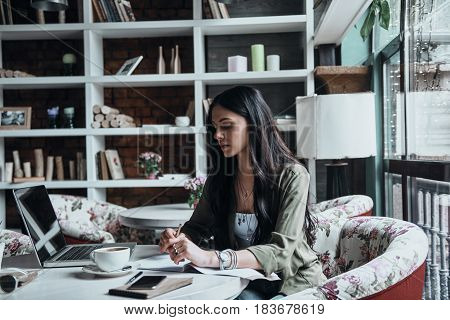 Writing down her thoughts. Thoughtful young woman writing something down in her notebook while sitting at her working place