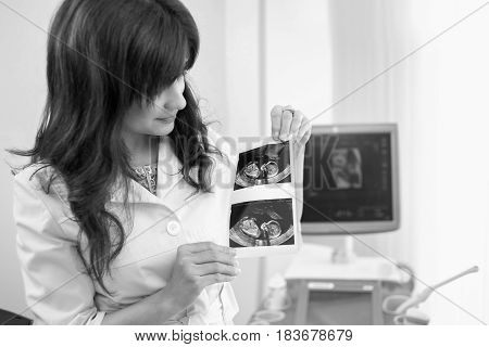 Monochrome shot of a female gynecologist looking at sonogram photo of an unborn child