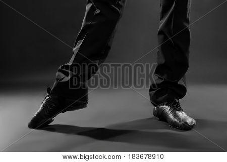 Legs of handsome young dancer on dark background