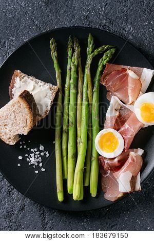 Cooked green asparagus with half boiled egg, sliced bread and ham bacon served with sea salt on black ceramic plate over dark stone texture background. Top view, fine dining