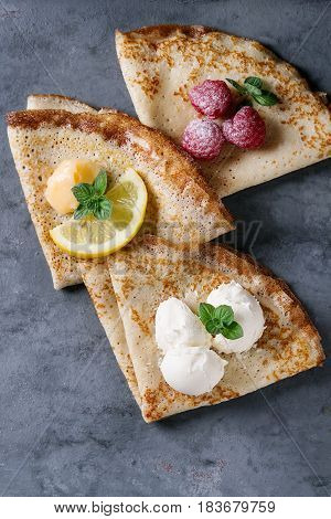 Sweet crepes pancakes with different fillings fresh raspberries, lemon curd, mascarpone cheese, mint, sugar powder over gray blue metal texture background. Top view with space