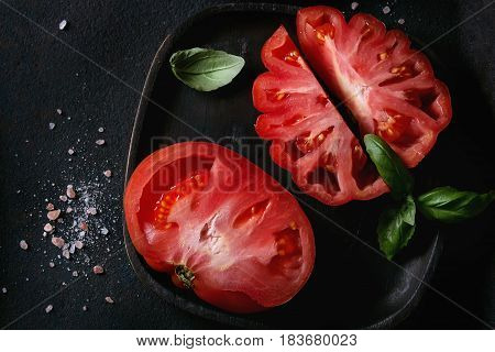 Whole and sliced organic tomatoes Coeur De Boeuf. Beefsteak tomato with pink salt and basil on black wooden plate over dark metal texture background. Top view with space.