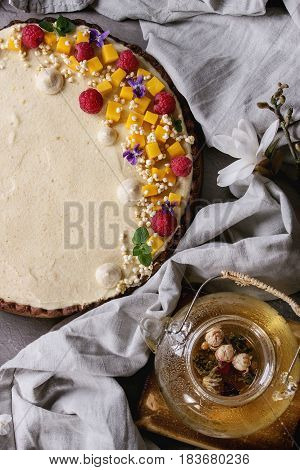Homemade chocolate tart decorated by mango, raspberries, mint, puffed rice and edible flowers served with glass teapot and textile linen over gray texture table. Top view. Comfort food concept.
