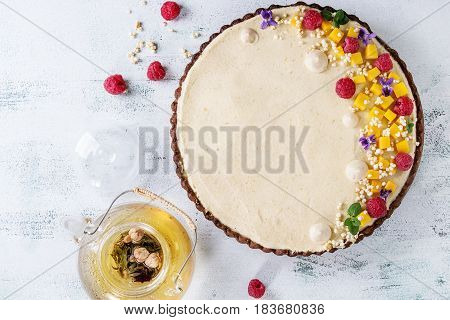 Homemade chocolate tart decorated by mango, raspberries, mint, puffed rice and edible flowers served with glass teapot over white texture wooden background. Top view with space.