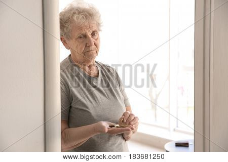 Senior woman counting coins at home. Poverty concept