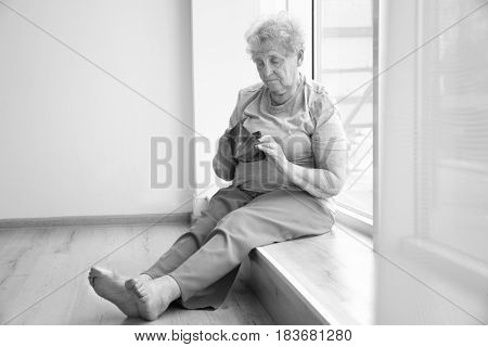 Senior woman sitting on window sill with empty purse. Poverty concept