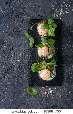 Verrines appetizer with salmon pate, red caviar, cucumber, cream cheese, herbs, capers in glasses served with pink salt and basil on black slate stone board over gray texture background. Top view