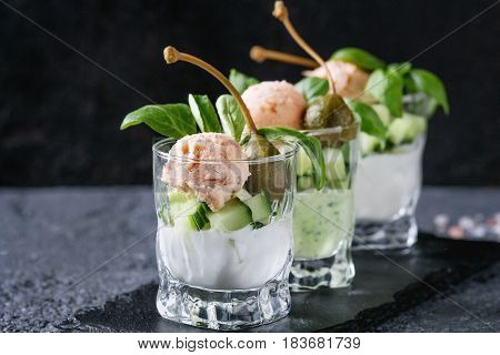 Verrines appetizer with salmon pate, red caviar, cucumber, cream cheese, herbs, capers in glasses served with pink salt and basil on black slate stone board over gray texture background.