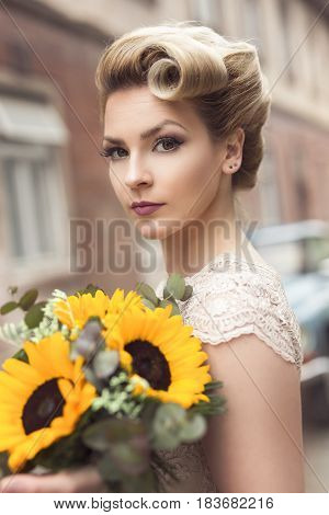 Beautiful young bride posing in a wedding dress in a retro cobble street with an old timer car in the background holding a sunflower bouquet