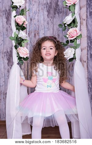 Cute little girl swinging on a cradle with flowers