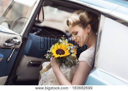 Beautiful young bride sitting in a wedding dress in a retro old car holding a sunflower bouquet