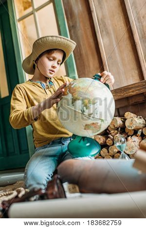Cute Little Boy Traveler In Hat Holding Globe While Sitting On Porch