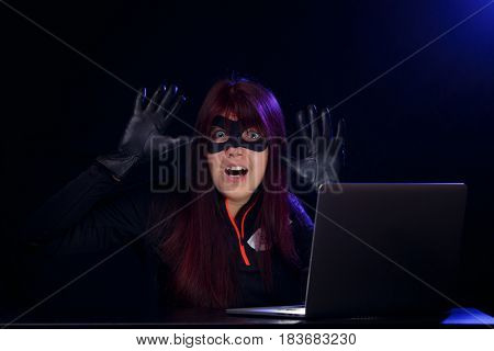 Brunette hacker with raised hands