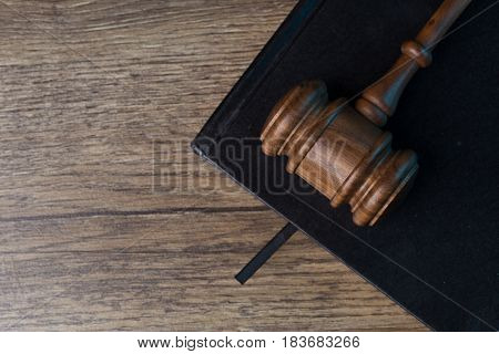 Judge's hammer on black notebook