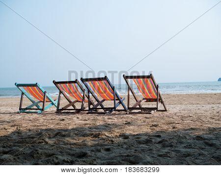 Four deck chairs on beach