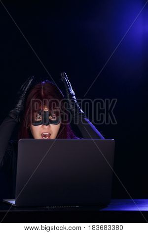 Young brunette hacker with laptop
