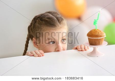 Cute little girl near table with birthday cake at home