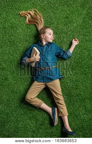 Top View Of Cute Little Girl With Book Lying On Green Grass, Education Kids Concept