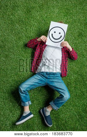 Top View Of Kid Lying On Grass And Covering Face With Picture