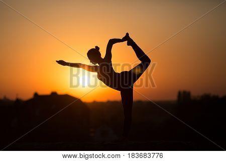 Slim Woman Doing Yoga Over Orange Sun