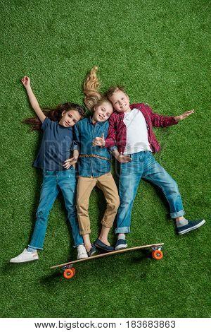 Top View Of Children Pretending Standing On Skateboard On Green Grass