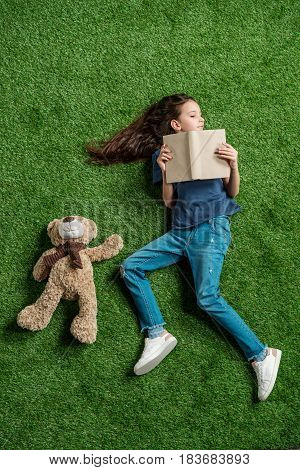 Top View Of Little Girl With Teddy Bear Holding Book While Lying On Grass, Education Kids Concept