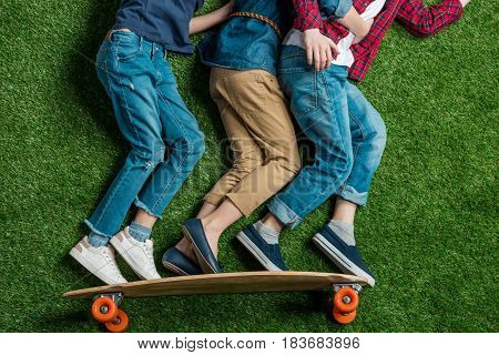 Partial View Of Children Pretending Standing On Skateboard On Green Grass