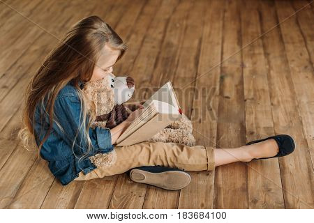 Side View Of Little Girl With Teddy Bear Reading Book, Education Kids Concept