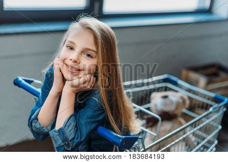 Portrait Of Smiling Girl Sitting In Shopping Cart