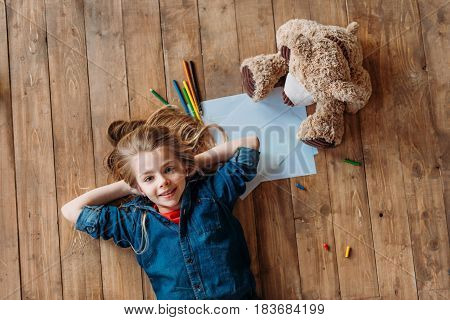 Top View Of Smiling Girl Lying On Floor With Teddy Bear And Pencils, Kids Drawing Concept