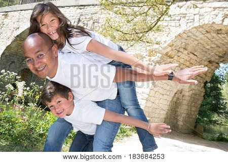 father and mixed son makes a piggyback with girl daughter metis and pretty
