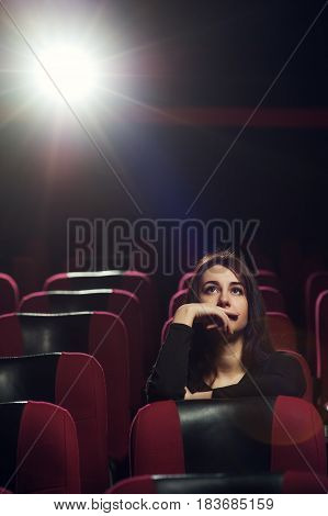 Beautiful brunette girl sitting in empty cinema theater. Young serious woman watching movie alone. Cinema, entertainment and leisure concept.