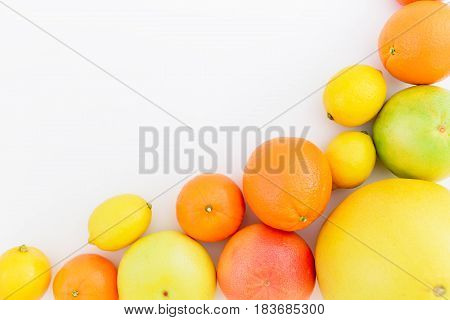Tasty frame made of fresh lemon, orange, mandarin, grapefruit, sweetie and pomelo fruit on white background. Flat lay, top view.