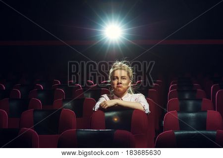 Portrait of cute blonde girl sitting in empty cinema hall, watching movie. Cinema, entertainment and leisure concept.