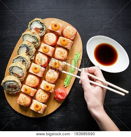 Japanese traditional food. Sushi rolls, sauce, wasabi and woman hand with chopsticks on dark background. Top view. Flat lay.