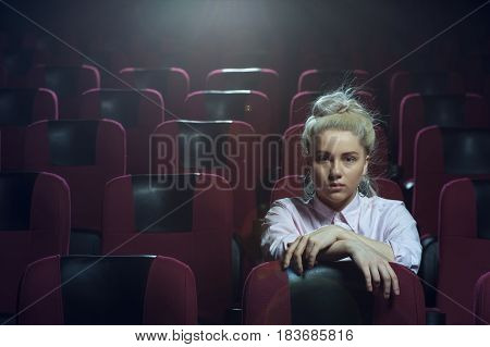 Young serious blonde girl sitting in empty cinema theater and watching movie. Cinema, entertainment and leisure concept.