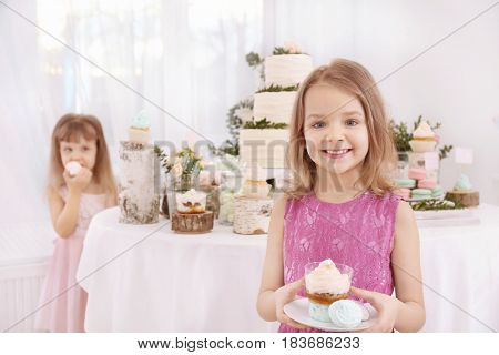 Cute little girl with sweets at party