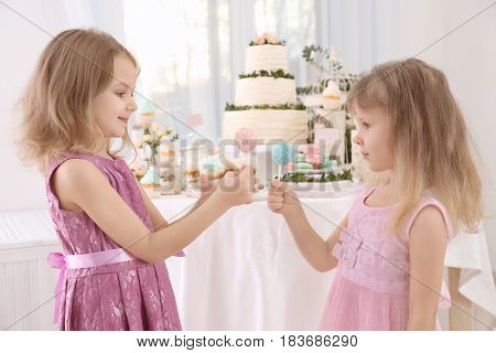 Cute little girls with tasty cake pops at party