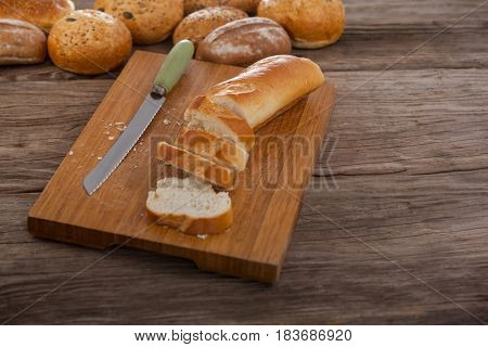 Sliced baguette with knife on wooden background