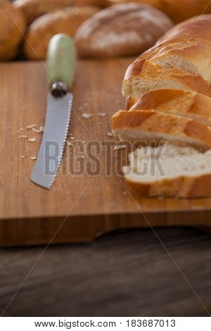 Close-up of sliced baguette with knife on wooden background