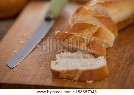 Close-up of sliced baguette with knife on cutting board