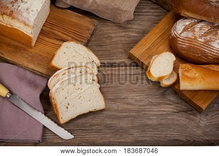 Various bread loaves with slices on wooden background
