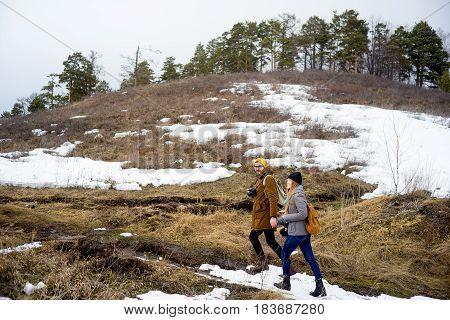 Two photographers hiking on a mountain lake