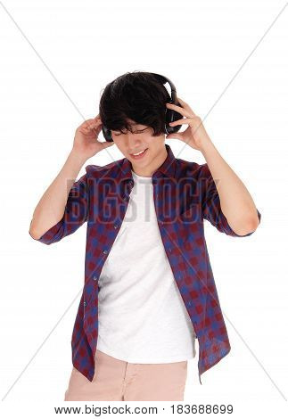 A young handsome Korean teenager listen to music with his headset in a checkered shirt isolated for white background.