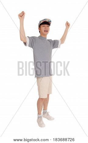A young Korean teenager standing in shorts an t-shirt with his arms raised for happiness isolated for white background.