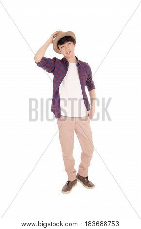 A happy Korean teenager standing in an checkered shirt holding a hat on his head isolated for white background.