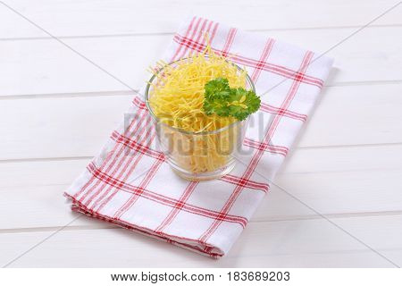 glass of dry soup noodles on checkered dishtowel