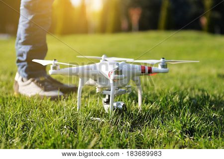 Ukraine Poltavskaya region Kremenchuk - April 26 2017: Man controls a quadrocopter. Launching a quadrocopter DJI Phantom 3 Standard in the park. Preparation quadrocopter to fly.